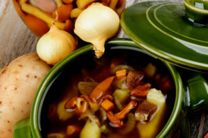 Homemade Delicious Vegetarian Soup with Chanterelle Mushrooms in Green Pot with Lid and Raw Ingredients closeup on Wooden background